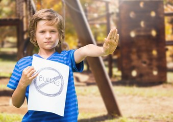 Sad boy holdingn anti bullying sign  against playground