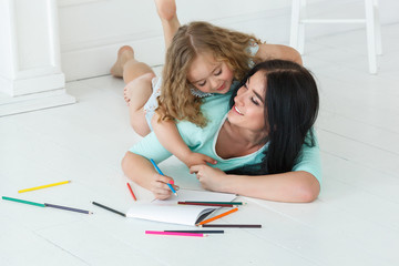 Little daughter and her mother are drawing with colorful pencils. Young pretty mom and her daughter educating and having fun