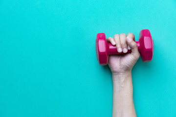 woman hand holding red dumbbell on green background
