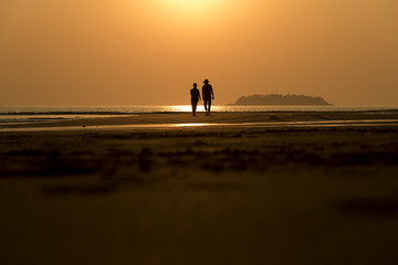 Silhouettes of tourists that are walking along the beach during sunset .