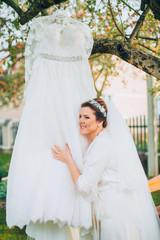 Bride in robe near wedding dress on tree outdoor in the garden backyard house.