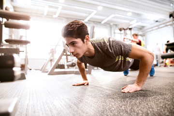 Young fit hispanic man in gym doing push ups