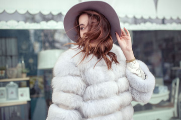 Happy smiling young woman outside in trendy hat and fur coat. Early spring weather.