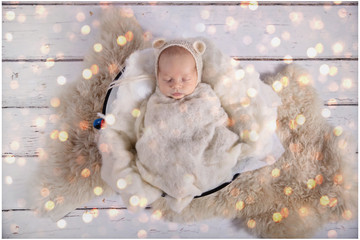 A baby boy is peacefully sleeping during his first professional photoshoot. He is dressed in white and covered with a white blanket.