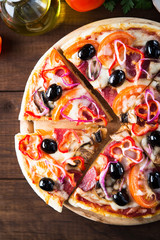 Sliced italian pizza with salami, mushroom, tomatoes, sweet pepper, black olives and purple onion on dark wooden background top view. Italian traditional food. Popular street food.