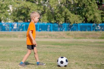 little boy in orange shirt playing soccer, kicking the ball