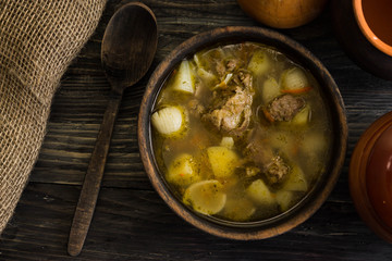 Soup with meat in a wooden bowl on a wooden table. Tasty and nutritious dish.