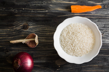 Raw rice in a white bowl on a wooden table and ingredients