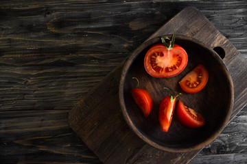 Sliced tomato in a wooden bowl on a wooden background in rustic style