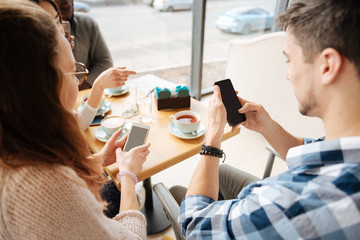 Positive friends using smartphones in tha cafe