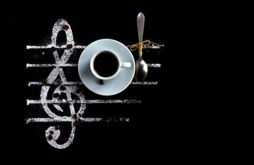 Black coffee in a cup with a spoon on a black background as a concept of musical notes