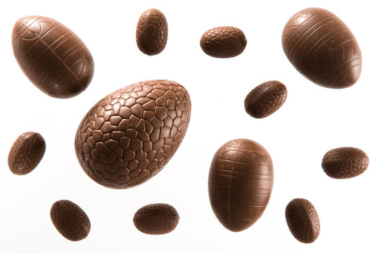 High angle view of a variety of unwrapped Easter chocolate eggs on a white background
