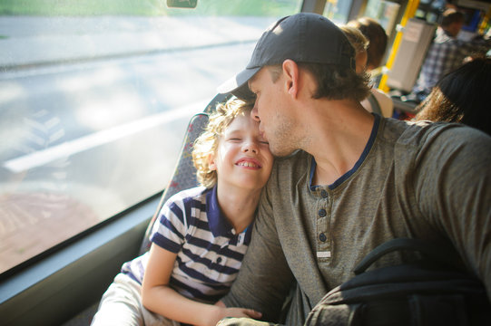 The young man goes by the bus together with the son.
