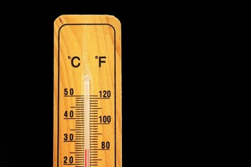 Thermometer on wooden base with celsius and fahrenheit scale isolated on black background.