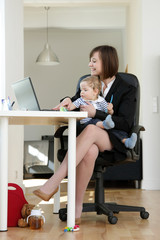 Lovely young working mother and her baby, in her Home Office