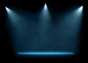 Three spotlights illuminating empty stage background.