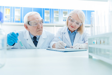 portrait of senior scientists working on experiment in lab