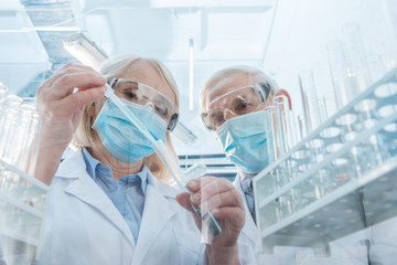 Senior couple of scientists making experiment in laboratory