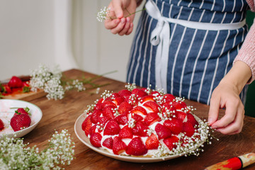 Woman decorating cake in stawberries and gypsophila