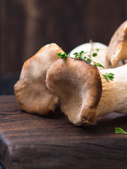 Mushrooms eringi with a branch of thyme on a brown wooden board
