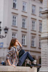 Fashion girl is sitting outdoors wearing blue jeans,brown checkered jacket and holding a brown handbag, urban city