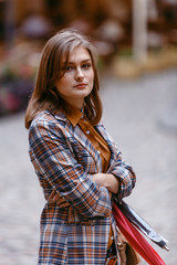 Fashion girl is walking on the sidewalk wearing blue jeans,brown checkered jacket and holding a brown handbag, urban city