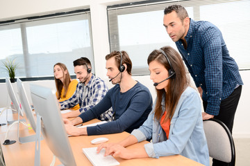 group of young people with desktop computer in row and headset training with teacher instructor in customer service call support helpline business center