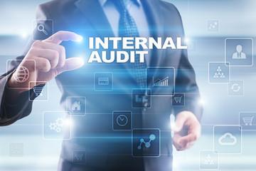 Businessman selecting internal audit on virtual screen.