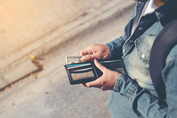 Hipster man hands holding wallet with credit cards and stack of money.