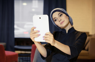 Beautiful oriental girl in Muslim clothes photographing herself on an electronic tablet