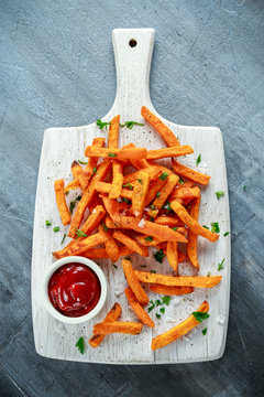 Healthy Homemade Baked Orange Sweet Potato Fries with ketchup, salt, pepper on white wooden board