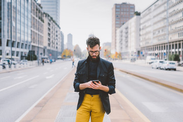Young bearded man using smart phone outdoor in the city - technology, business, social network concept