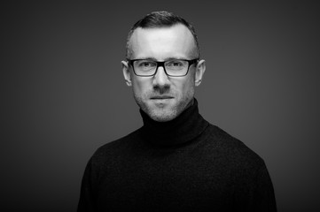 Obraz portret mężczyzny w studio na ciemnym tle w okularach - fototapety do salonu