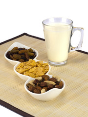a glass of milk with dried fruits and flakes.
