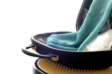 Beauty case put open on a chair. containing a green pareo and a white bikini