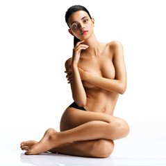 Beautiful young naked woman sitting over white background. Photo of tanned brunette with perfect skin. Beauty and body care concept