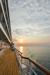 Cruise ship wooden promenade deck with beautiful sunset  and reflection on the ocean.