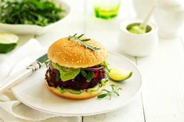Vegetarian vegetable burger with beetroot and guacamole sauce.
