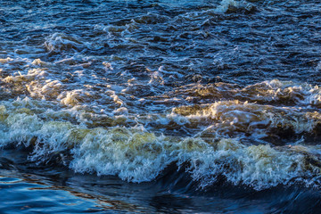 Wave on a fast river in the sunset. There is foam on the waves. Natural background Wallpaper. Plenty of space for text.
