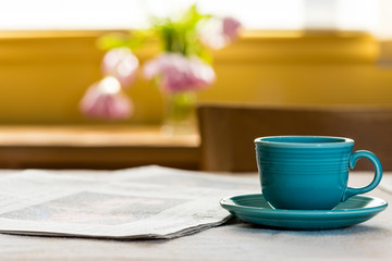Cup and saucer on table near newspaper with tulips and window light in the background.