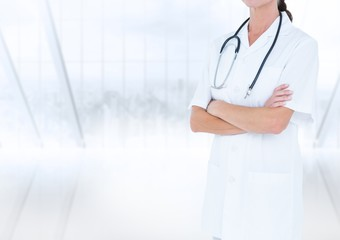 Doctor mid section with arms folded against blurry window
