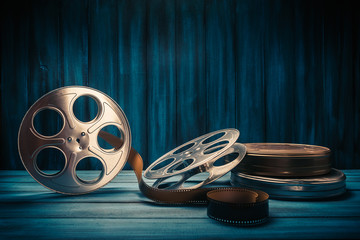 movie reels and cans with dramatic lighting on a wooden background