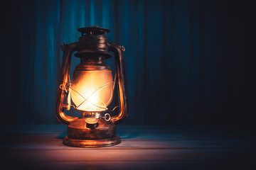 kerosene lamp on a wooden background with dramatic lighting