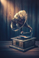 Old Gramophone with dramatic lighting on a wooden background