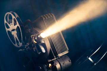 movie projector on a wooden background with dramatic lighting and selective focus