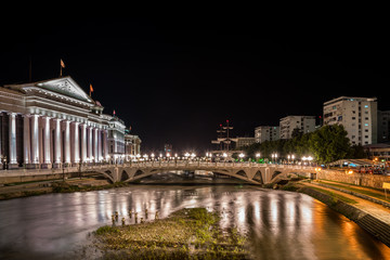Night view of the Center of Skopje Macedonia with the river Vardar in the foreground, stone bridge with many statues and lights.