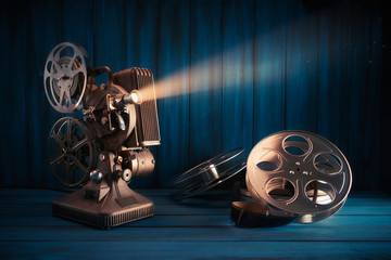 vintage 8mm movie projector with 35mm reels and film on a wooden background with dramatic lighting
