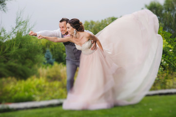 Newlyweds in a superman pose on a green lawn background, park.