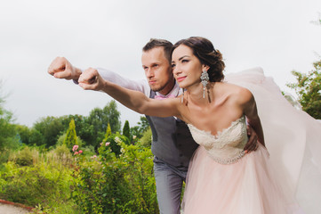 Newlyweds in a superman pose