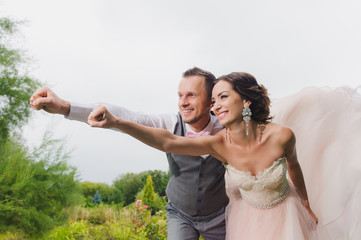 Newlyweds in a superman pose on a green lawn background, park. Average plan.